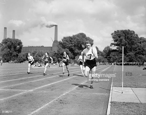 British athlete Heather Armitage running in Battersea Park with the chimneys of the famous power station behind her