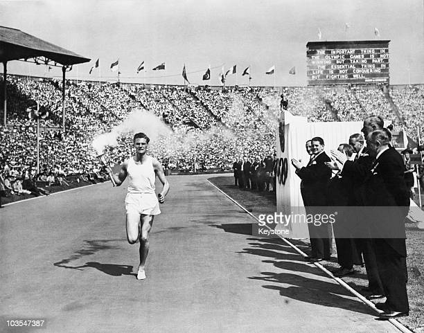 British athlete John Mark carries the Olympic torch into Wembley Stadium at the opening ceremony of the 1948 Olympic Games London 29th July 1948