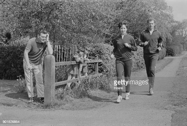 British athletes Ann Packer and Robbie Brightwell running past a front yard UK 23rd May 1968