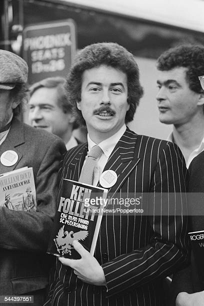 British author and novelist Ken Follett pictured wearing a pin stripe suit and holding a copy of his book 'The Man from St Petersburg' at Victoria...