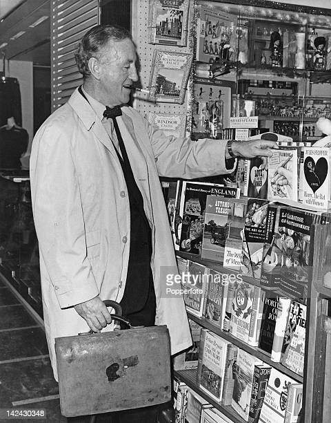 British author Ian Fleming creator of the James Bond series of spy novels picks up a copy of his novel 'On Her Majesty's Secret Service' in a shop at...