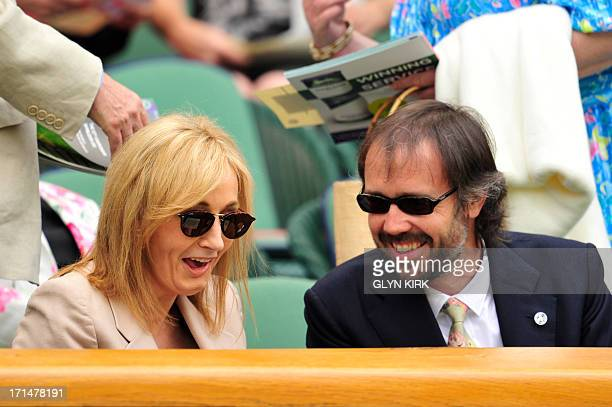 British author J K Rowling sits on centre court with her husband Neil Murray ahead of the start of play on day two of the 2013 Wimbledon...