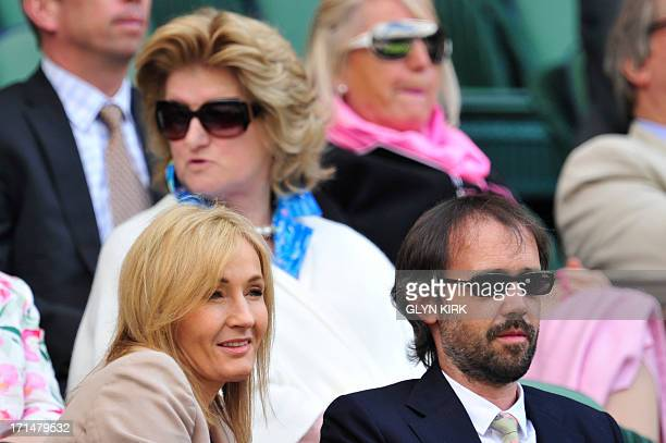 British author J K Rowling sits watching the action on centre court with her husband Neil Murray during play on day two of the 2013 Wimbledon...