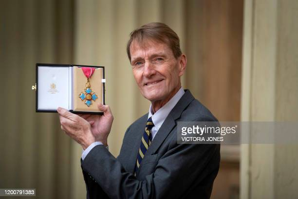 British author James Grant, better known as Lee Child, poses with his medal after he was appointed a Commander of the Order of the British Empire at...