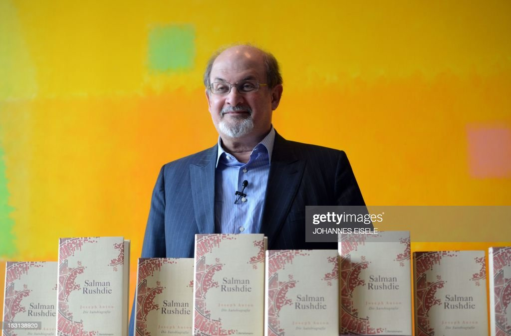 British author Salman Rushdie poses behind some copies of his book 'Joseph Anton' on October 1, 2012 in Berlin. As violent protests over a US-made film rock the Muslim world, Salman Rushdie publishes his account of the decade he spent in hiding while under a fatwa for his book 'The Satanic Verses'.