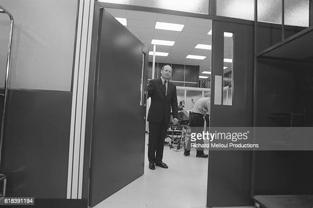 British auto racing manager Ron Dennis opens the door of a studio where the MP4/14 car is being assembled at the McLaren F1 workshops in Woking