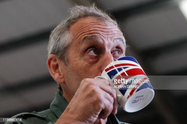 British aviator Steve Brooks drinks from a Union Flag mug as he is interviewed by media before take off on a roundtheworld flight attempt in a...