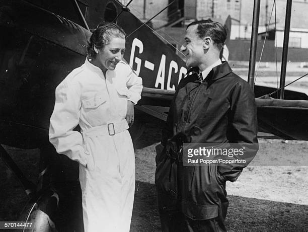 British aviators and spouses Amy Johnson and Jim Mollison standing next to a small plane after a flight circa 1935