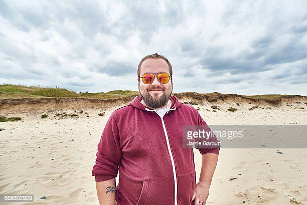 british bearded male smiling happily on the beach - muscle men at beach stock photos and pictures