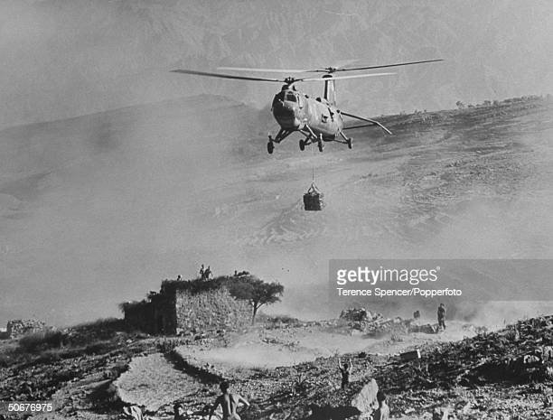 British Belvedere helicopter dropping jerrigans of water to Paratroopers during battle for Rebel positions