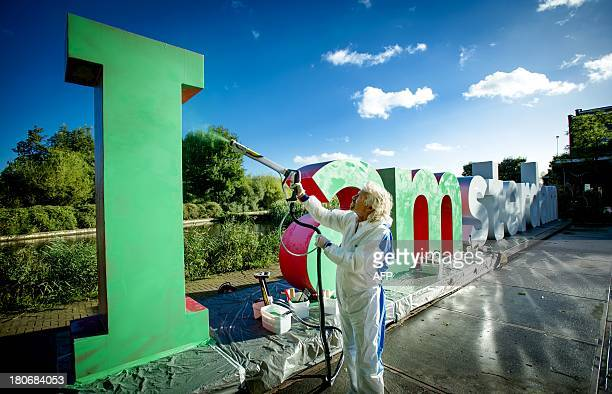 British billionaire Richard Branson spraypaints in green the I of the Amsterdamlogo on September 16 2013 at the Westergasterrein in Amsterdam as he...