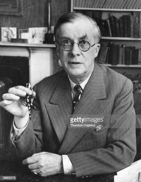 British biologist and writer Dr Julian Huxley posing with a fire salamander one of the animals appearing in his television programme titled 'Animal...