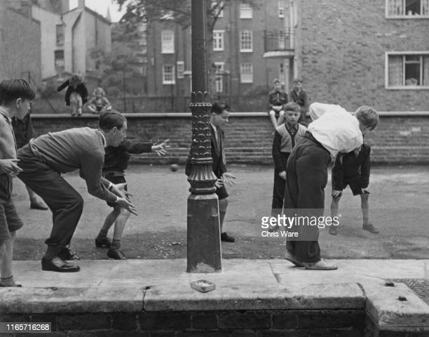 British bishop and cricket player David Sheppard , curate at St Mary's Church, playing cricket, as wicket-keeper, with local boys in the street,...