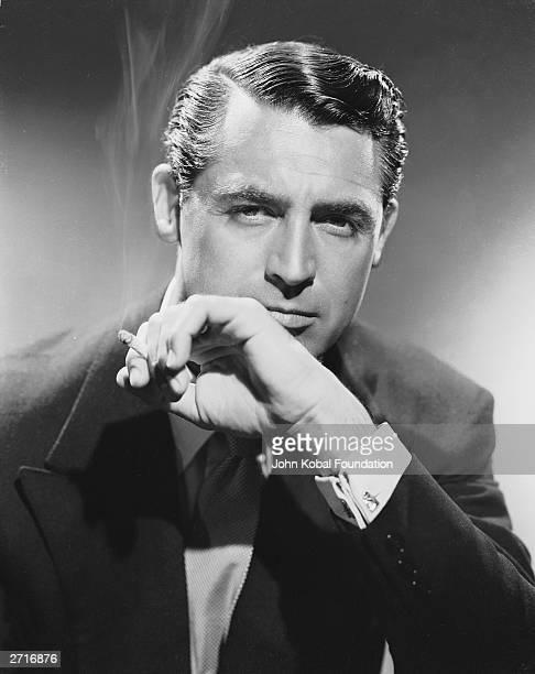 British born actor Cary Grant , born Archibald Leach, smoking a cigarette.