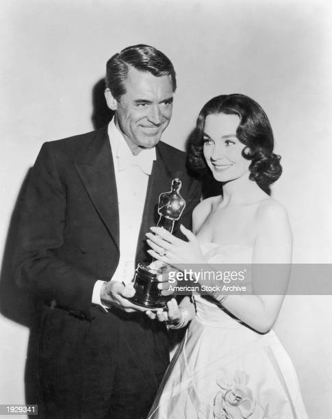 British born actor Cary Grant presents British actor Jean Simmons with the Best Actor award, which she accepts on behalf of Alec Guinness for the...