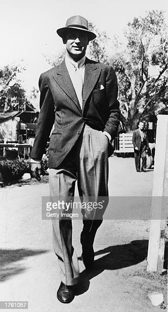 British born actor Cary Grant walking outdoors wearing a pinstripe jacket and a hat 1940s