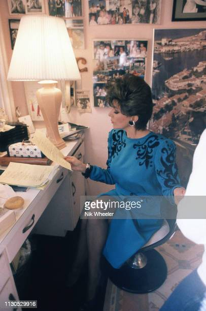 British born actress and TV star Joan Collins reads script in her dressing room on the set of hit show soap opera Dynasty in which she plays villain...
