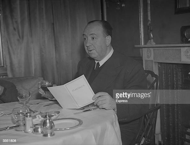 British born film director and producer Alfred Hitchcock drinking a glass of wine as he reads the menu at Claridges in London
