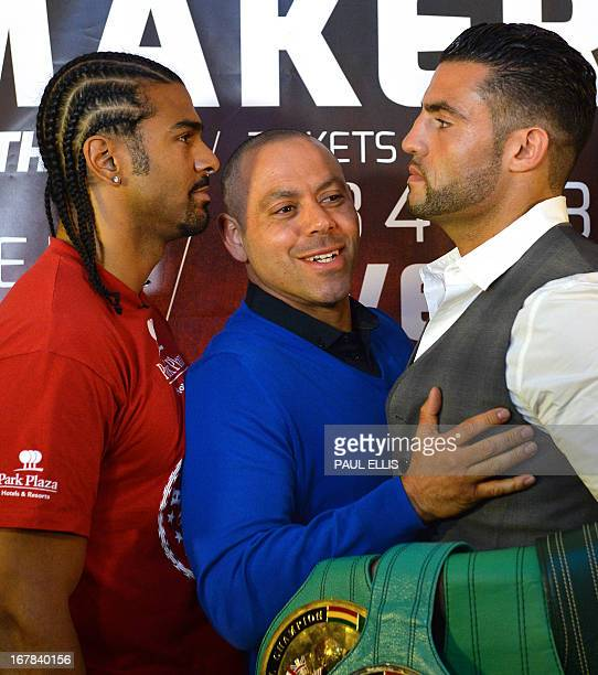 British boxer David Haye's trainer Adam Smith steps in between him and German boxer Manuel Charr during a press conference in Manchester England on...