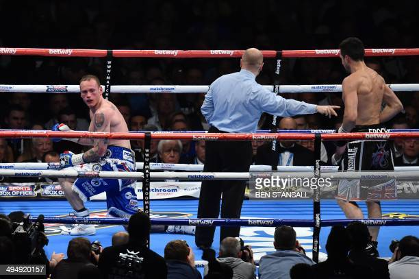 British boxer George Groves goes on one knee after being knock down by British boxer Carl Froch during their WBA and IBF supermiddleweight title bout...