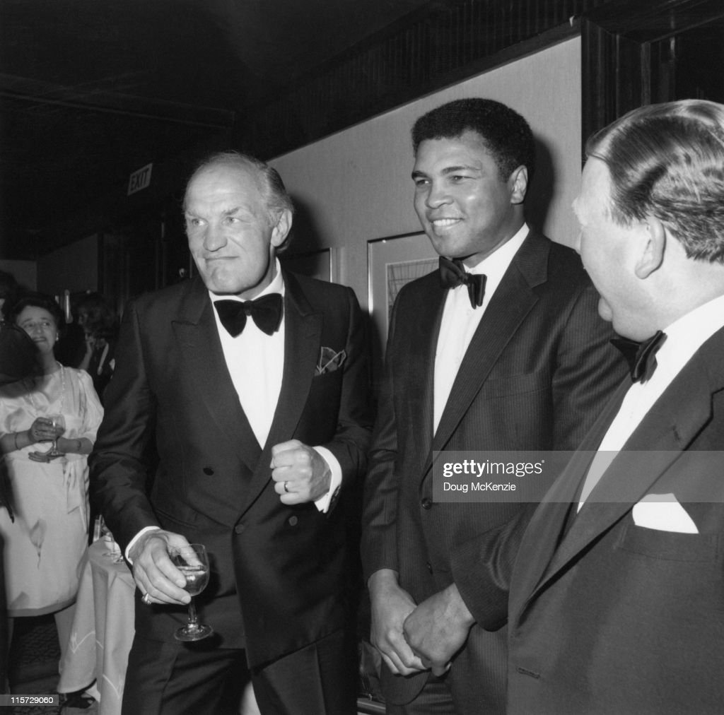British boxer Henry Cooper (1934 - 2011, left) at a function with his old rival Muhammad Ali (centre), 1984.