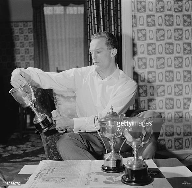 British boxer Henry Cooper cleaning his trophies at his home in Bellingham south London 19th November 1958