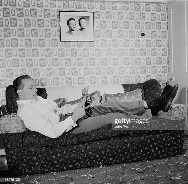 British boxer Henry Cooper relaxing at his home in Bellingham south London 19th November 1958 On the wall is a portrait of Cooper with his twin...