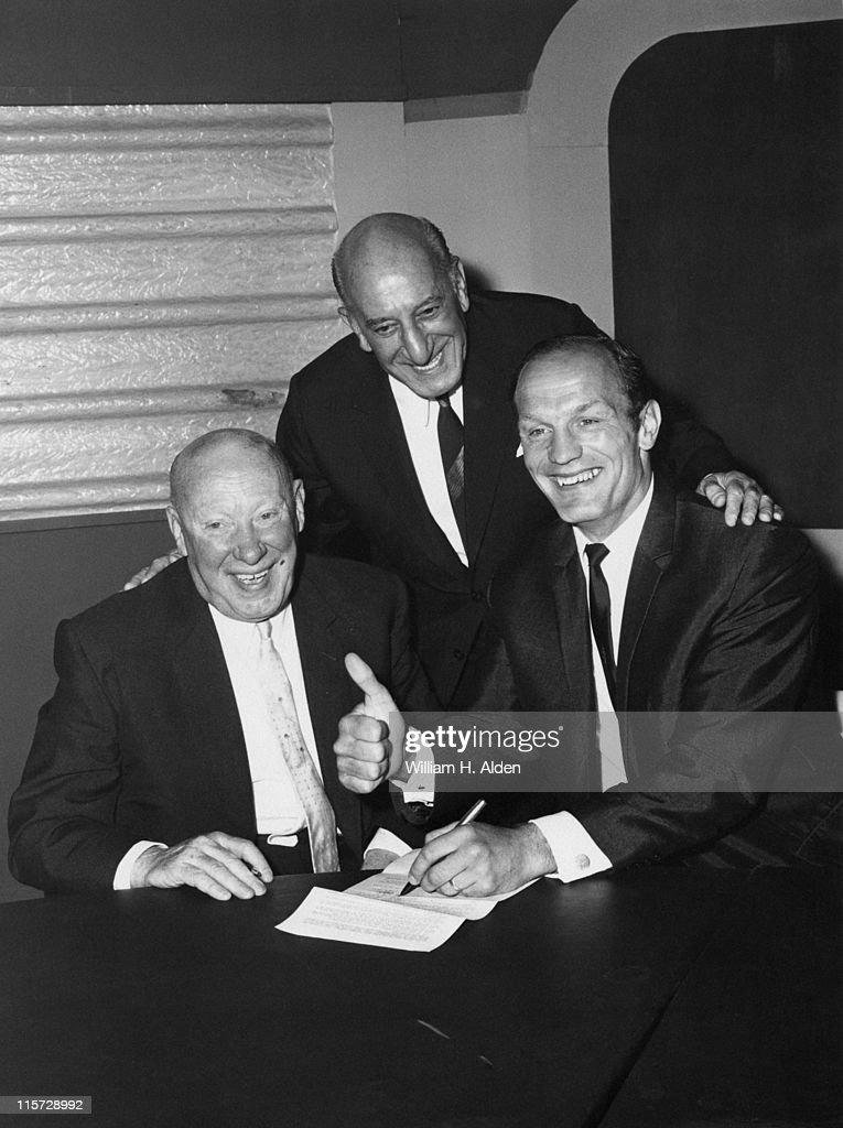 British boxer Henry Cooper (1934 - 2011, right) signing a contract for a WBA fight against Jimmy Ellis of the USA, 15th August 1969. Left to right: Cooper's trainer Jim 'The Bishop' Wicks, promoter Harry Levene and Cooper. The match with Ellis never took place.