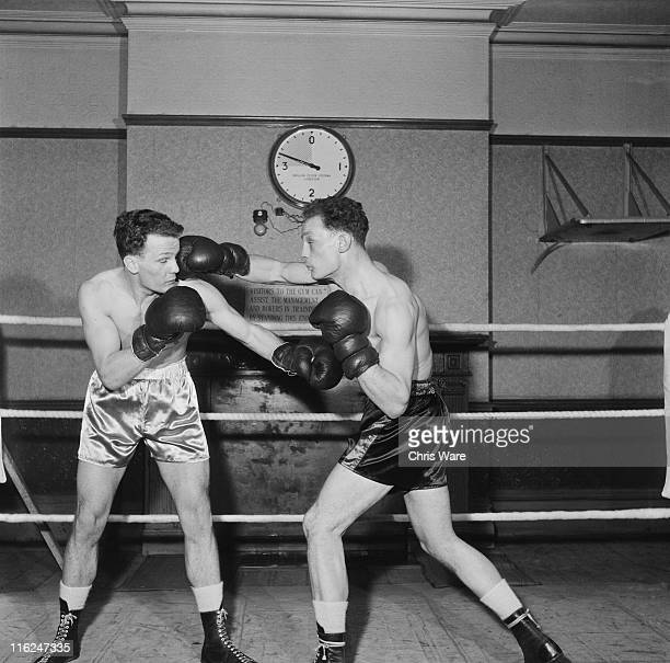 British boxer Henry Cooper sparring with his twin brother George at a gym run by their manager Jim Wicks in South London 9th February 1955 George...