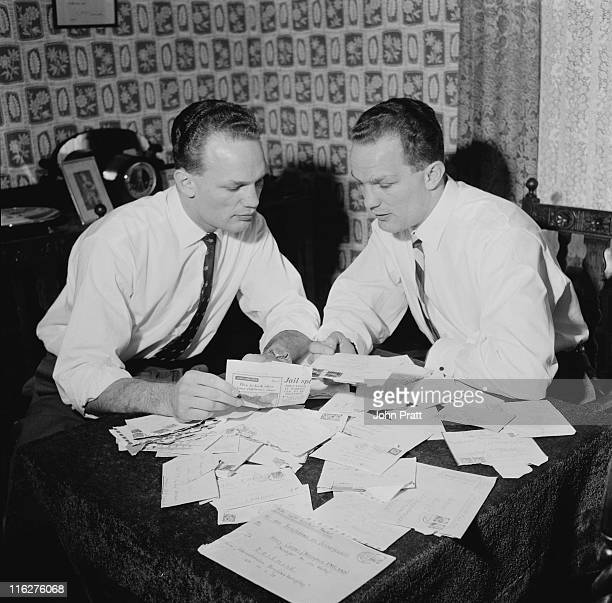 British boxer Henry Cooper with his twin brother George going through fan mail at their home in Bellingham south London 19th November 1958 George...