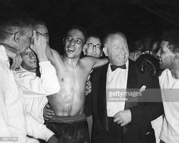 British boxer Randolph Turpin and his promoter Jack Solomons celebrate Turpin's win over Sugar Ray Robinson in the World Middleweight Championship at...