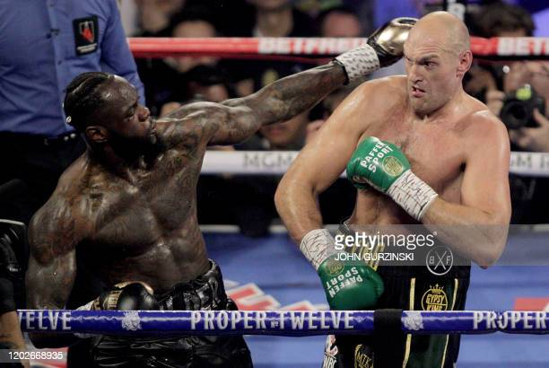 British boxer Tyson Fury and US boxer Deontay Wilder exchange punches during their World Boxing Council Heavyweight Championship Title boxing match...