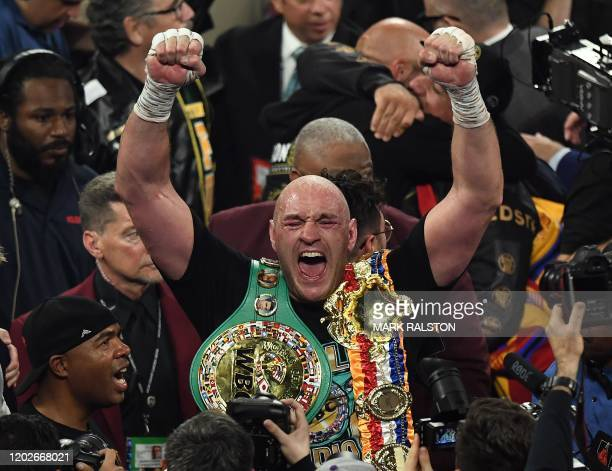 TOPSHOT British boxer Tyson Fury celebrates after defeating US boxer Deontay Wilder in the seventh round during their World Boxing Council...