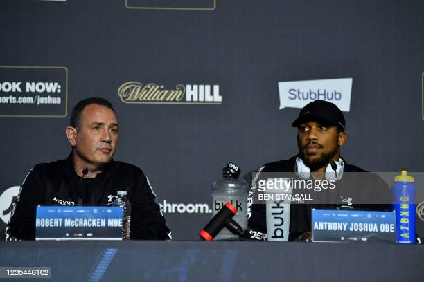 British boxing trainer Robert McCracken MBE and British heavyweight champion boxer Anthony Joshua attend a press conference at Tottenham Hotspur...