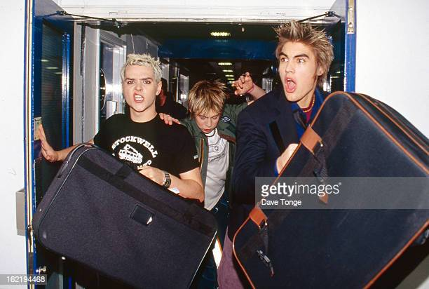British boy band Busted run through a corridor backstage at TV show CD UK London 2002 Left to right Mattie Jay James Bourne and Charlie Simpson