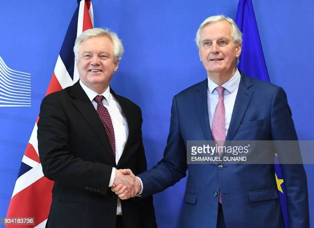 British Brexit minister David Davis and EU chief negotiator Michel Barnier shake hands as they meet at the European Commission in Brussels on March...