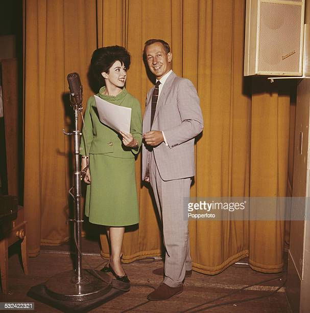 British broadcaster and disc jockey Brian Matthew pictured standing with singer Susan Maughan at a microphone in a recording studio in 1962