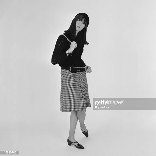 British broadcaster Cathy McGowan presenter of the music televsion programme Ready Steady Go pictured wearing a checked skirt and blouse in London in...