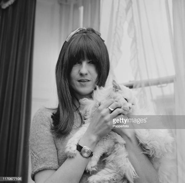 British broadcaster Cathy McGowan presenter of the music televsion programme Ready Steady Go holds a long haired cat at home in April 1966