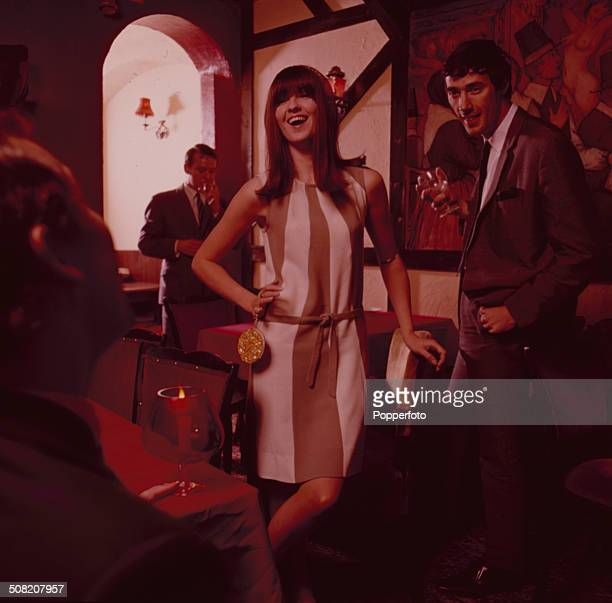 British broadcaster Cathy McGowan wearing a cream and brown striped dress poses with three men in a club in 1965