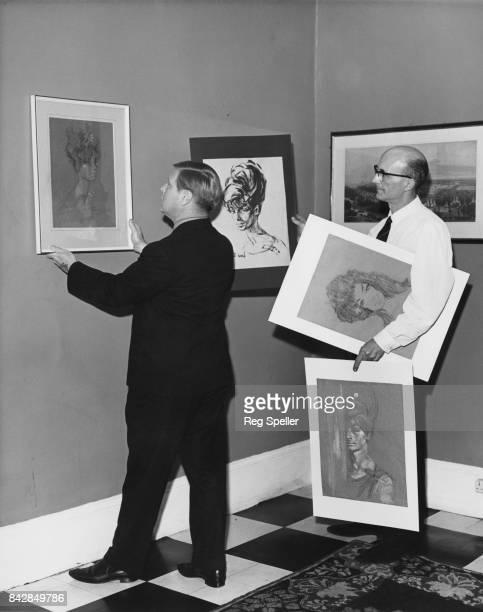 British broadcaster Daniel Farson hangs portraits of Adele de Havilland by osteopath Stephen Ward in his pub the Waterman's Arms in Millwall London...