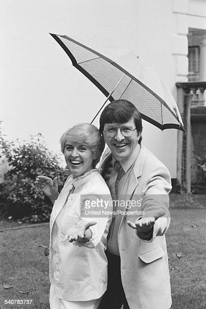 British broadcasters and presenters of the BBC television series Saturday Live Gloria Hunniford and Simon Bates pictured together under an umbrella...