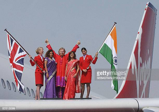 British business tycoon Sir Richard Branson of Virgin Atlantic Airways is surrounded by air hostesses and Indian models holding the British and...