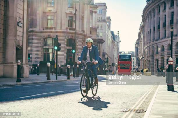 british businessman commuting to work by bicycle - cycling stock pictures, royalty-free photos & images