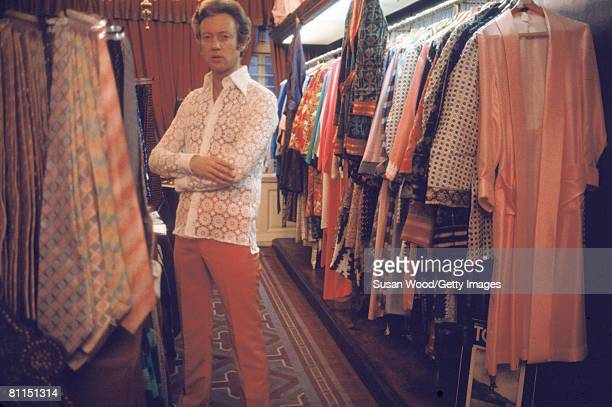 British businessman John Barry Sainsbury poses among racks of clothing and kipper ties in the 'Mr Fish' boutique that he founded with designer...