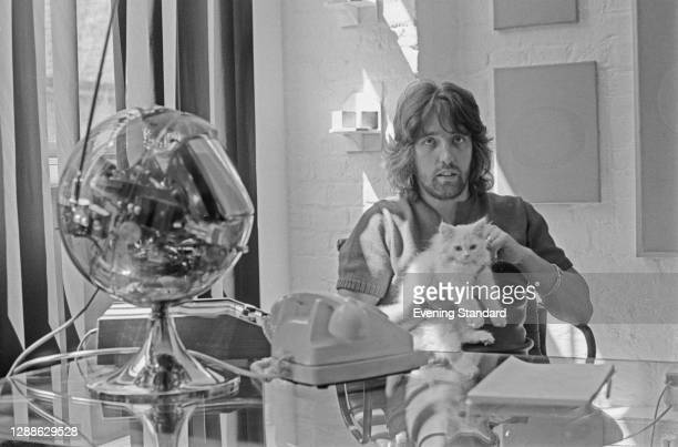 British businessman Justin de Villeneuve, the manager of supermodel Twiggy, with a white cat and a spherical transparent television, UK, July 1971.