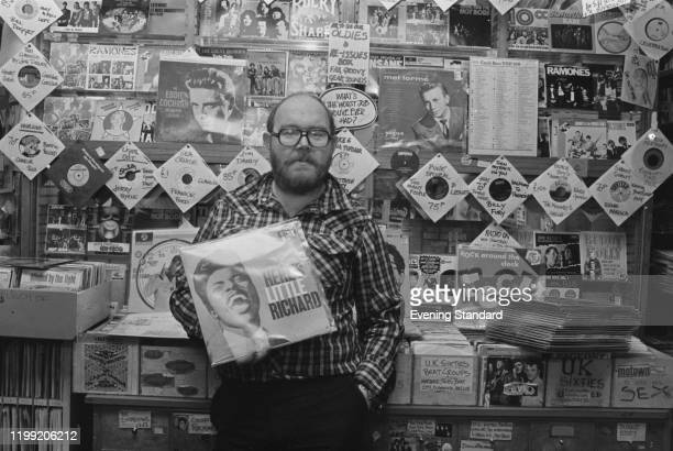 British businessman Ted Carroll cofounder of Ace Records holding a copy of 'Here's Little Richard' in Rock On Records in Camden London England in...