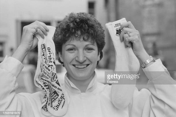 British businesswoman Sophie Mirman, co-founder of Sock Shop, poses holding up a pair of socks in each hand, 1st November 1984.