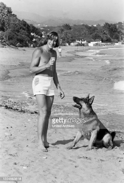 British car racing driver James Hunt with his pet dog on the beach, circa 1974.