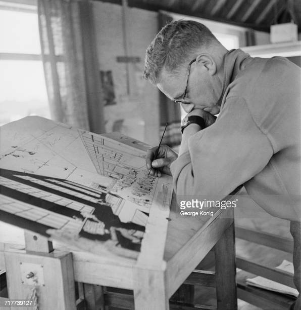 British cartoonist Carl Giles at work in his studio on his farm in Suffolk, June 1948. Giles is best known for his work for the Daily Express and...